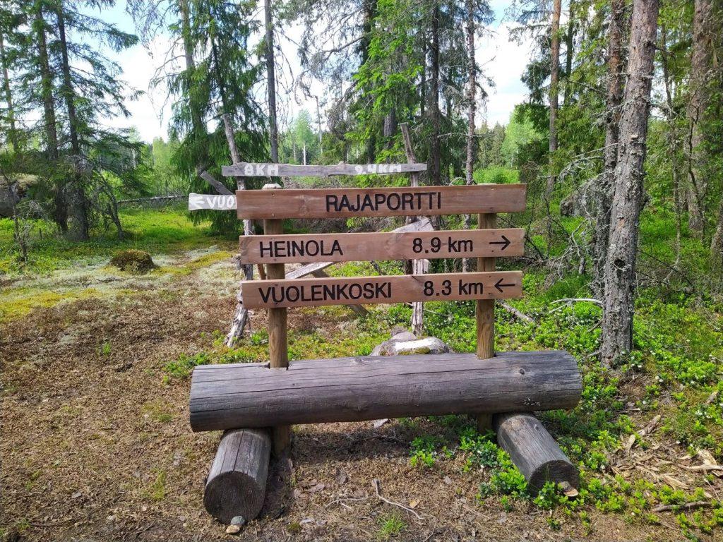 Rajaportti, Iitin ja Heinolan rajalla. Heinola 8,9 km, Vuolenkoski 8,3 km. Puukyltit.